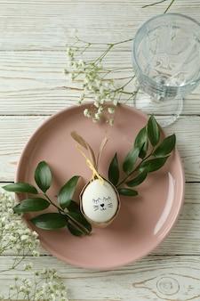 Счастливой пасхи сервировка стола с пасхальным кроликом из яйца на деревянном столе