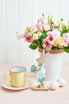 Happy easter table with eggs, rabbit and flowers.