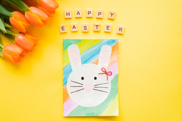 Happy easter text wooden letters and hand-made easter card and orange tulips on yellow background.