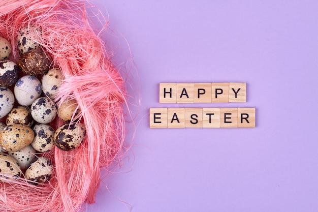 행복 한 부활절 소원과 메추라기 알의 둥지. 부활절 축하 개념입니다. 보라색 배경에 고립.