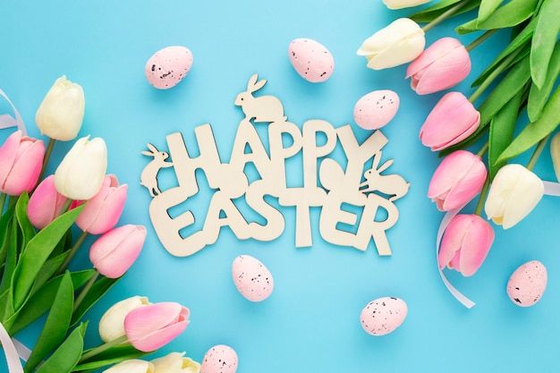 Happy easter wooden sign with tulips on a blue background