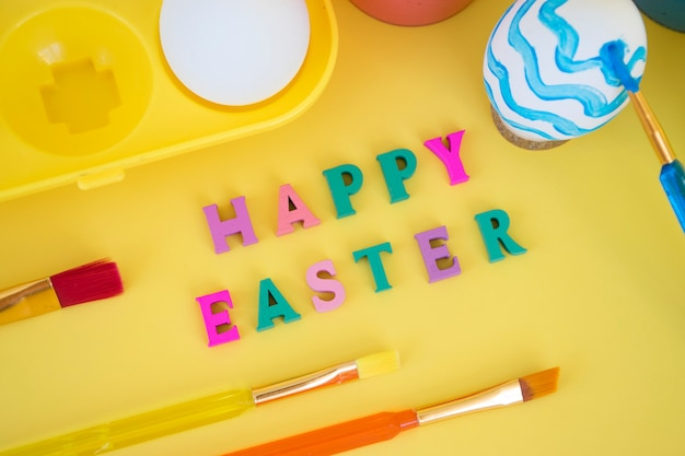 Happy easter word made of colorful letters with eggs in yellow egg tray, paints and brushes paitning egg in blue waves on yellow wall.