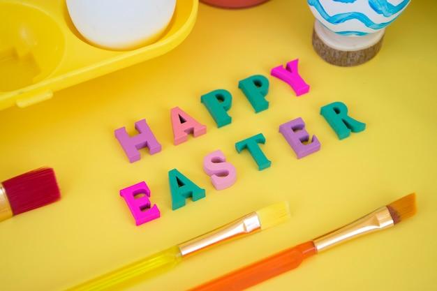 黄色の卵トレイに卵が入ったカラフルな文字で作られたハッピーイースターワード、黄色の青い波で卵を塗る塗料とブラシ