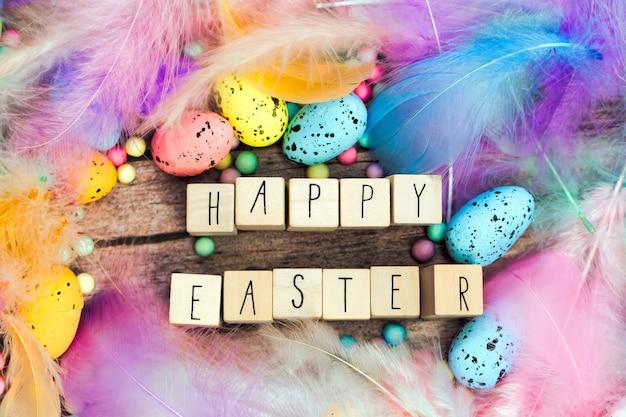 아름다운 파스텔 컬러 장식 깃털과 계란으로 둘러싸인 나무 큐브로 작성된 행복한 부활절
