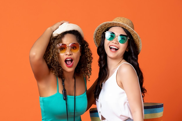 Happy ecstatic interracial woman friends in summer casual clothes