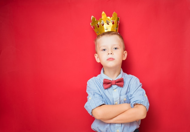 Happy education and childhood concepts with an adorable 6-year old boy holding a golden king crown on his head as a wise spoiled child