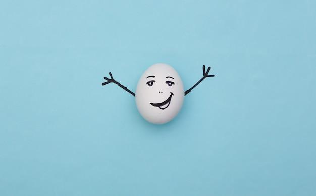 Счастливое яйцо с рисованным лицом на синем фоне