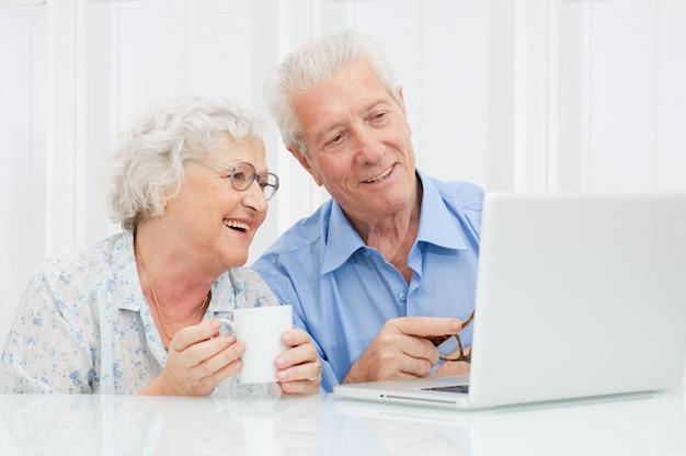 幸せな高齢者のカップルがラップトップコンピューターで一緒に楽しむ