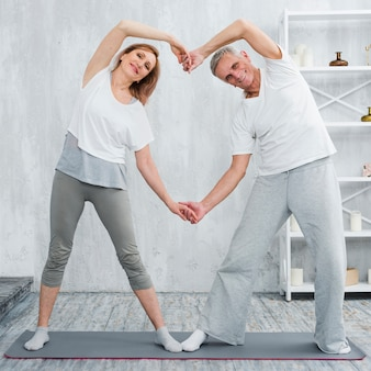Happy elder couple standing on yoga mat at home