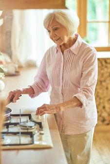 Happy elder lady standing in the kitchen and preparing food