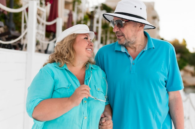 Happy elder tourist couple on the beach