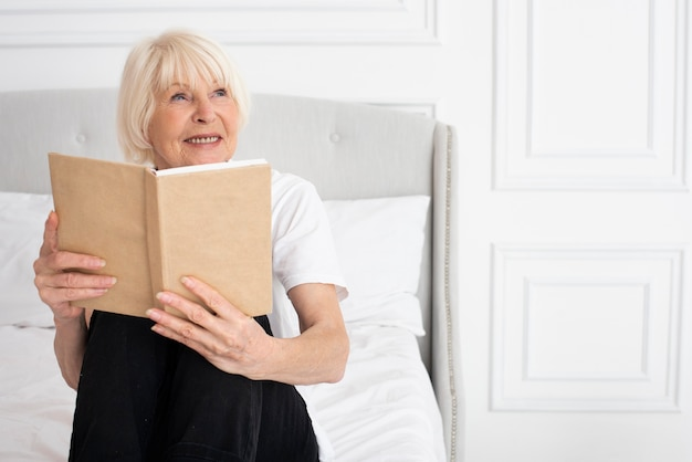 Happy elder woman holding a book