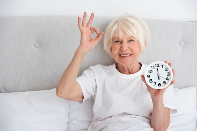 Happy elder woman holding a clock in her bed
