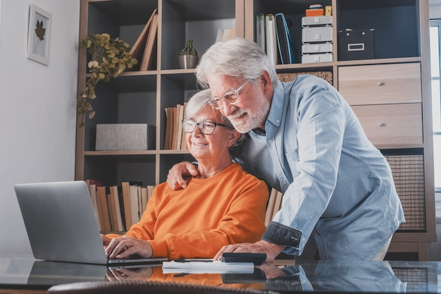 Happy elderly 60s couple sit rest on couch at home pay household expenses online on computer