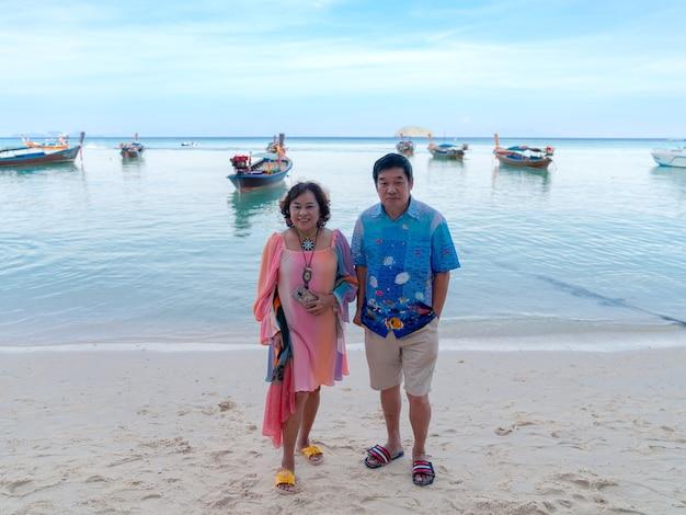 다채로운 옷을 입은 행복한 아시아 노부부 가족, 태국 리페 섬의 바다 해변에 서 있는 연인, 보트가 보이는 하얀 모래 푸른 바다, 여름에는 휴식