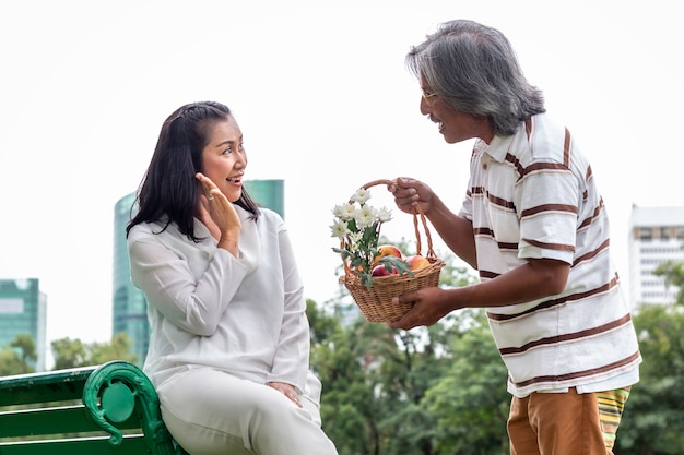Happy elderly asian couple with fruit basket in park.