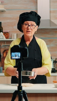 Happy elderly baker woman filming cooking vlog in home kitchen. retired blogger chef influencer using internet technology communicating, shooting blogging on social media with digital equipment