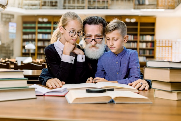 Happy elderly bearded man, grandfather and his cute grandson and granddaughter are sitting at the table in vintage old library and reading books.