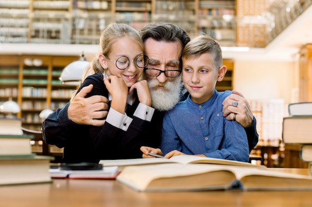 Happy elderly bearded man, grandfather and his cute grandson and granddaughter are sitting at the table in vintage old library and reading books