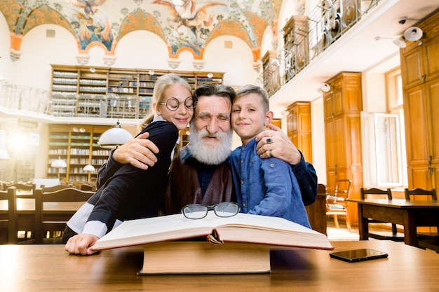 Happy elderly bearded man with his two cute granddaughter and grandson in library. grandpa and his charming teen grandchildren spending time in the library reading interesting book