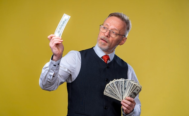 Happy elderly business man with fan of dollar bills