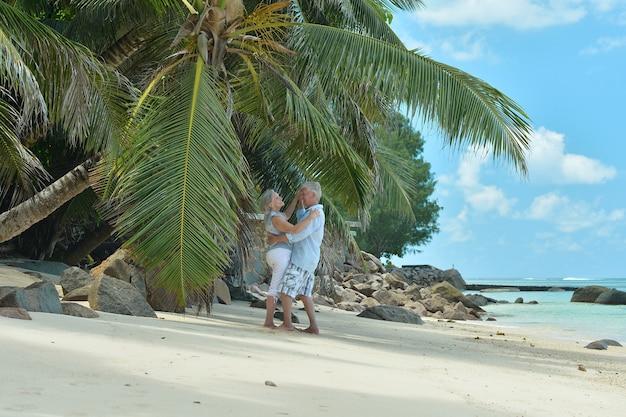 熱帯のビーチで踊る幸せな老夫婦