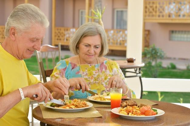 Happy elderly couple having breakfast outdoors together