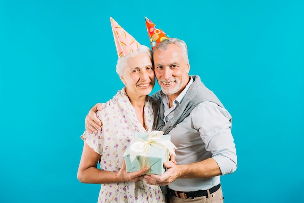 Happy elderly couple holding birthday gift on blue background