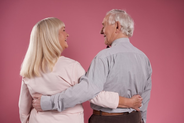 Happy elderly couple hugs each other from back.