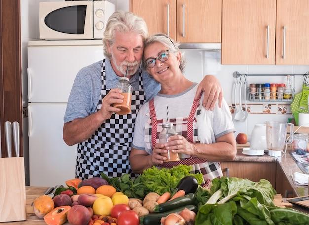 作ったばかりのジュースフルーツを楽しんでいる幸せな老夫婦。夫は妻を抱きしめます。カラフルな果物や野菜の大規模なグループと木製のテーブル。健康的な食事