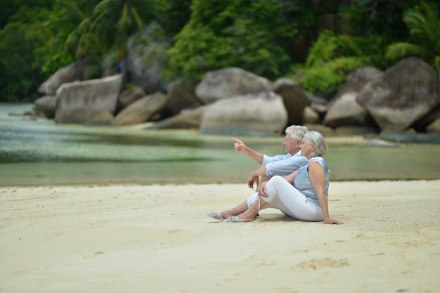 幸せな老夫婦が熱帯のビーチで休む、彼の手で指している男