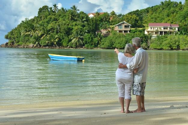 幸せな老夫婦は熱帯のビーチで休む、彼女の手で示す女性