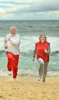 ビーチで走っている幸せな老夫婦
