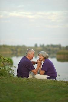 공원에서 잔디에 앉아 행복 한 노인 커플