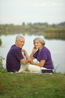 公園の芝生の上に座って幸せな老夫婦