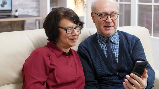 Happy elderly couple sitting on sofa holding smartphone during a video call.