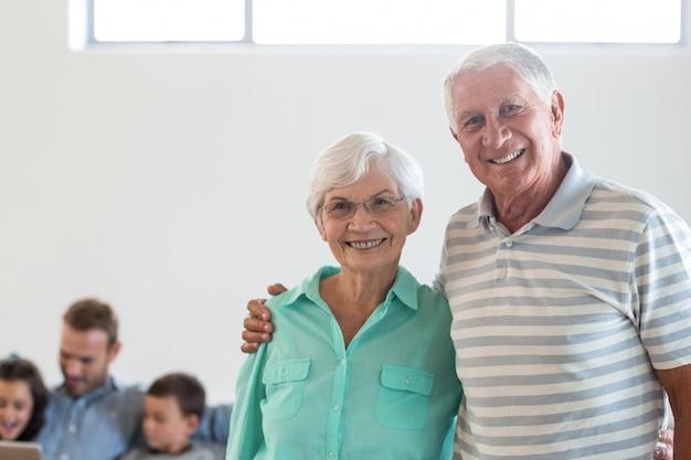 Счастливая пожилая пара, улыбаясь в камеру