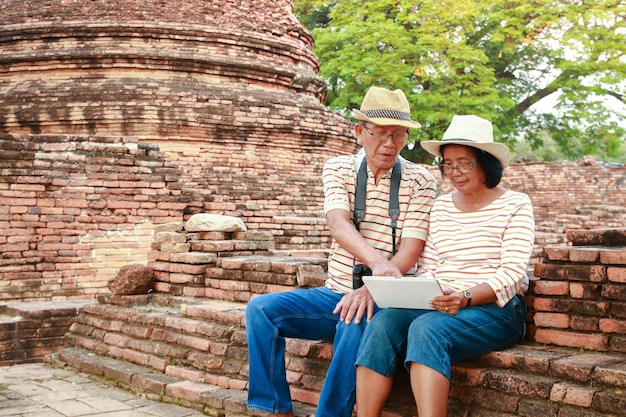 Happy elderly couple travel ancient archaeological sites with history in asia