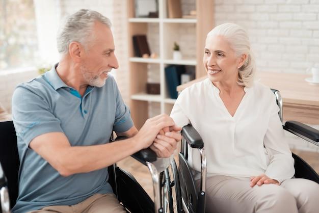 Happy elderly couple in wheelchair hold hands.