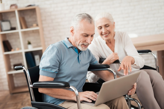 Happy elderly couple in wheelchairs looks at laptop screen.