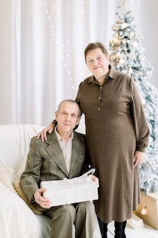 Счастливая пожилая пара с подарочной коробкой на фоне елки вместе празднует рождественские праздники