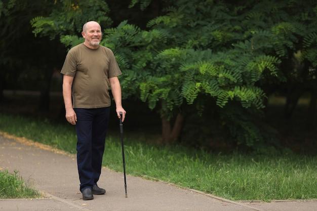 幸せな高齢者は、夏に屋外の杖で歩く男を無効に