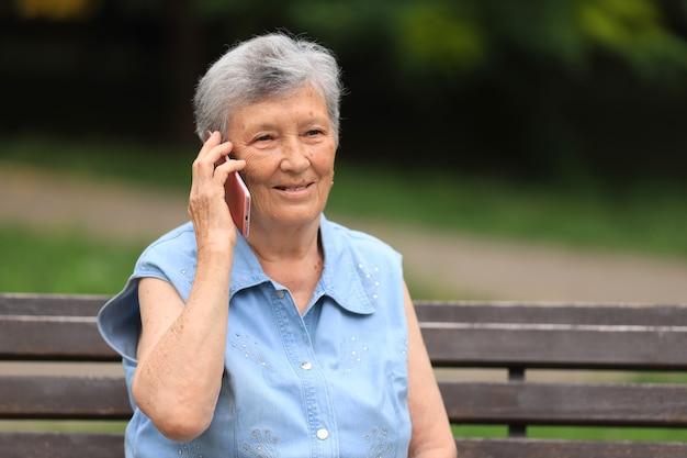 Счастливая пожилая женщина-инвалид, сидящая на скамейке на открытом воздухе в летнем парке и разговаривающая по телефону