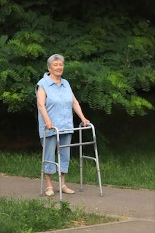 Счастливая пожилая женщина-инвалид гуляет с ходунками на открытом воздухе летом