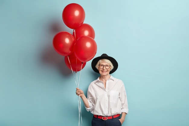 Happy elderly female in festive clothes, holds bunch of air balloons, celebrates anniversary, waits for children and guests, enjoys celebration, poses over blue wall. pensioner on party