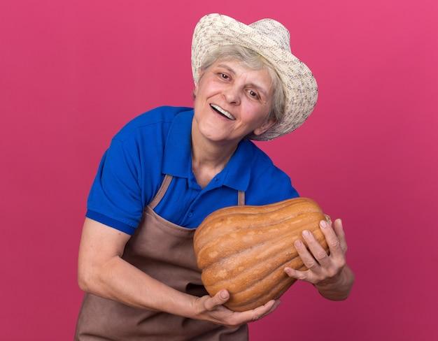 Felice giardiniere femminile anziano che indossa cappello da giardinaggio che tiene zucca