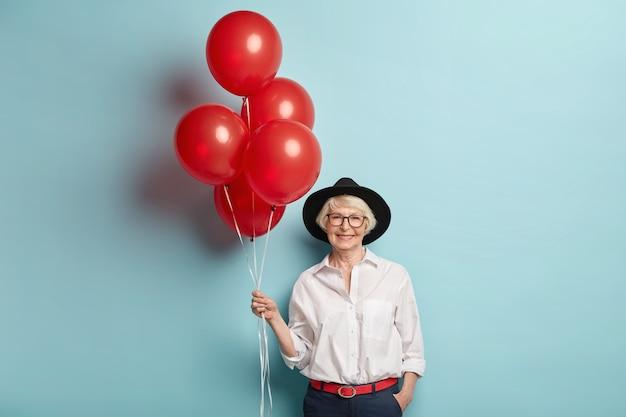 축제 옷을 입은 행복한 노인 여성, 공기 풍선 잔뜩 들고, 기념일을 축하하고, 어린이와 손님을 기다리고, 축하를 즐기고, 파란색 벽 위에 포즈를 취합니다. 파티 연금