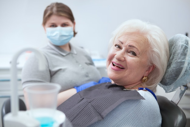 Счастливая пожилая дама улыбается в камеру после стоматологического осмотра в клинике