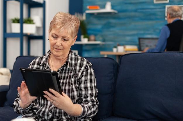 ビデオ通話中にスマートフォンで手を振っている幸せな老婦人。リビングルームのソファに座ってビデオ会議の過程で電話のウェブカメラで手を振っている年配の女性。