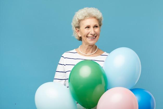 Счастливая пожилая дама с букетом воздушных шариков